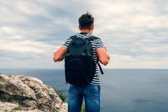Viaggiatore maschio con uno zaino su lei indietro che esamina il mare Fotografia Stock