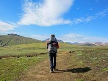 Viaggiatore maschio dalla parte posteriore nelle montagne con il grandi zaino e pannello solare immagine stock