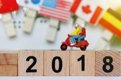 Viaggiatore miniatura con il motociclo sul blocco di legno con il numero 2018 concetto di corsa Immagine Stock Libera da Diritti