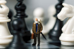 Viaggiatore miniatura e scacchi della bambola Viaggiatore anziano in scacchiera Immagini Stock Libere da Diritti