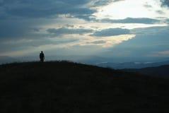 Viaggiatore solo attraverso le montagne Immagine Stock