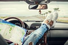 Viaggiatore solo dell'automobile della giovane donna con la mappa Immagini Stock