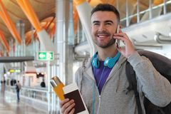 Viaggiatore sorridente che chiama dall'aeroporto Fotografia Stock