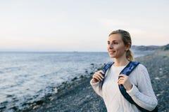 Viaggiatore sorridente della giovane donna in un abbigliamento bianco che sta sulla riva e sugli sguardi in mare Immagine Stock
