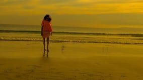 Viaggiatore su una spiaggia con il tramonto arancio dorato Fotografia Stock