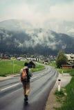 Viaggiatore sulla strada che va al villaggio alpino con lo zaino Fotografia Stock