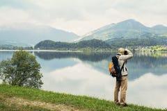 Viaggiatore sulla strada che va al villaggio alpino con lo zaino Immagine Stock