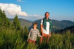 Viaggiatori allegri: un uomo e un ragazzo stanno stando su un meado alpino Fotografia Stock