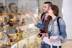 Viaggiatori che scelgono calzature dalla vetrina fotografia stock libera da diritti