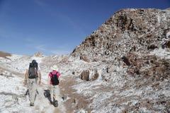 Viaggiatori con zaino e sacco a pelo che esplorano la valle della luna nel deserto di Atacama, Cile Fotografia Stock Libera da Diritti