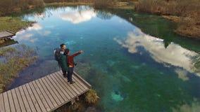 Viaggiatori con zaino e sacco a pelo che godono di bella vista intorno al lago video d archivio