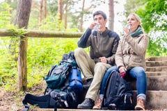 Viaggiatori con zaino e sacco a pelo che prendono resto e che hanno acqua minerale fotografia stock libera da diritti