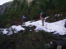 Viaggiatori con zaino e sacco a pelo delle donne che attraversano neve Fotografia Stock Libera da Diritti