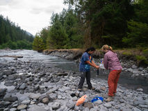 2 viaggiatori con zaino e sacco a pelo delle donne che filtrano acqua Immagine Stock Libera da Diritti