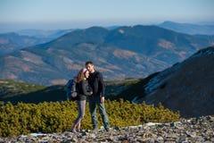 Viaggiatori con zaino e sacco a pelo felici delle coppie che godono delle montagne sui precedenti Immagini Stock