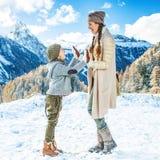 Viaggiatori del bambino e della madre nell'inverno all'aperto che gioca immagini stock libere da diritti