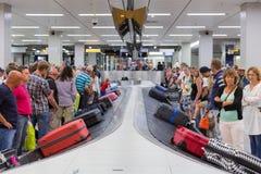 Viaggiatori dell'aeroplano che aspettano i loro bagagli all'aeroporto di Schiphol a Amsterdam, Paesi Bassi fotografia stock