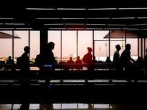 Viaggiatori della siluetta che camminano sul marciapiede mobile in termin dell'aeroporto immagini stock libere da diritti