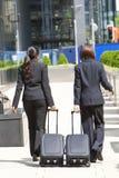 Viaggiatori di affari delle donne con le valigie di rotolamento Immagine Stock