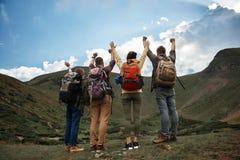 Viaggiatori felici che mettono le mani su dopo il raggiungimento della cima fotografia stock