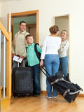 Viaggiatori positivi della famiglia con bagagli nella casa che va in vacanza immagine stock libera da diritti