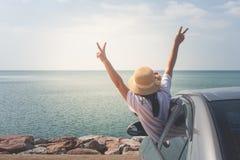 Viaggio al mare, donna dell'automobile di famiglia del ritratto allegra sollevando le sue mani su e ritenendo felicità immagini stock