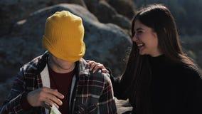 Viaggio alle montagne La bella coppia nell'amore si siede sulla roccia ed impara una mappa Parlano a vicenda, ridendo stock footage
