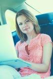 Viaggio d'affari: donna di affari occupata con il computer portatile in automobile Immagini Stock Libere da Diritti