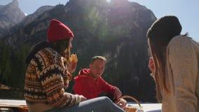 Viaggio dei giovani Amici che hanno picnic Sedendosi sulla costa e mangiare pane stock footage