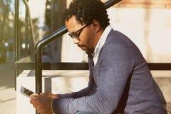 Viaggio dell'uomo d'affari, lavorante a New York Giovane ubicazione dell'uomo di colore sulla via, lettura, funzionamento sull'ap Immagine Stock Libera da Diritti