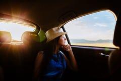 Viaggio della donna e sognare in macchina con luce solare e la v pittoresca immagini stock libere da diritti
