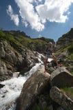 Viaggio della giovane donna con lo zaino in montagna Fotografie Stock