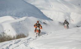 Viaggio di gatto delle nevi dello snowbike di enduro con la bici della sporcizia alta nelle montagne Immagine Stock