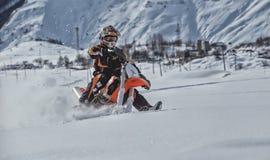 Viaggio di gatto delle nevi dello snowbike di enduro con la bici della sporcizia alta nelle montagne Fotografia Stock