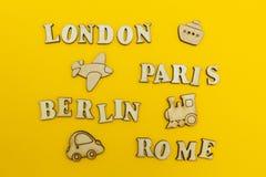 """Viaggio intorno ad Europa, i nomi delle città: """"Parigi, Londra, Berlino, Roma """"su un fondo giallo Figure di legno di un aeroplano fotografie stock"""