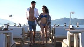 Viaggio romantico, coppia allegra che corre insieme sul molo contro il bello paesaggio del mare video d archivio
