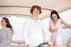 Viaggio, seatrip, amicizia e concetto della gente - amici che si siedono sulla piattaforma dell'yacht immagini stock