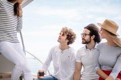 Viaggio, seatrip, amicizia e concetto della gente - amici che si siedono sulla piattaforma dell'yacht immagini stock libere da diritti
