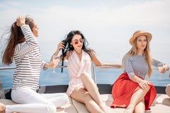 Viaggio, seatrip, amicizia e concetto della gente - amici che si siedono sulla piattaforma dell'yacht immagine stock