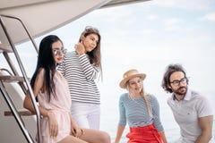 Viaggio, seatrip, amicizia e concetto della gente - amici che si siedono sulla piattaforma dell'yacht fotografie stock libere da diritti