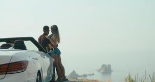 Viaggio stradale romantico L'uomo e la donna alla moda godono di bello paesaggio che sta prima di un'automobile da qualche parte  stock footage