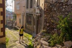 Viaggio turistico della donna in cappello e vetri del sole sulle vacanze estive che camminano nella vecchia città Alacati, Cesme, immagine stock