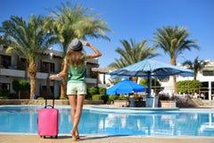 Viaggio, vacanze estive e concetto di vacanza - bella donna che cammina vicino all'area di stagno dell'hotel con la valigia rosa fotografie stock