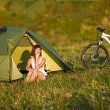 Viaja con la bicicleta sola - la mujer joven en la tienda Fotografía de archivo libre de regalías