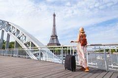 Viaja a excursão a Paris, Europa, mulher com a mala de viagem perto da torre Eiffel foto de stock