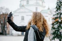 Viaja la ciudad vieja Viajes de una mujer joven Cuadrado de mercado en Varsovia La muchacha rizada camina a través de las calles  Foto de archivo