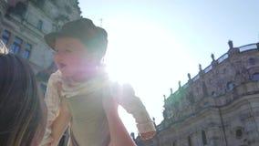 Viajando con los niños, la madre juega con el hijo joven en la calle en contraluz en el fondo del cielo