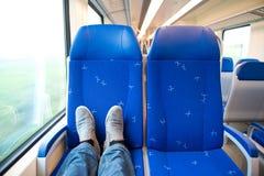 Viajando solamente en un trein, pies en los asientos Foto de archivo libre de regalías