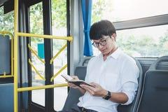 Viajante asiático novo do homem que senta-se em uma música e em um re de escuta do ônibus foto de stock