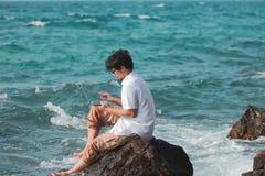 Viajante asiático novo do homem que usa o portátil na rocha do litoral natural Vacations o conceito do verão fotos de stock royalty free